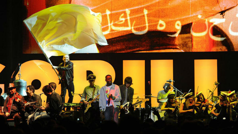 syrian-national-orchestra-of-arabic-music-damon-albarn-onstage-at-the-roundhouse-london-2010-with-members-of-the-syrian-national-orchestra-for-arabic-music-photographer-mark-allan-1280x720-1200px